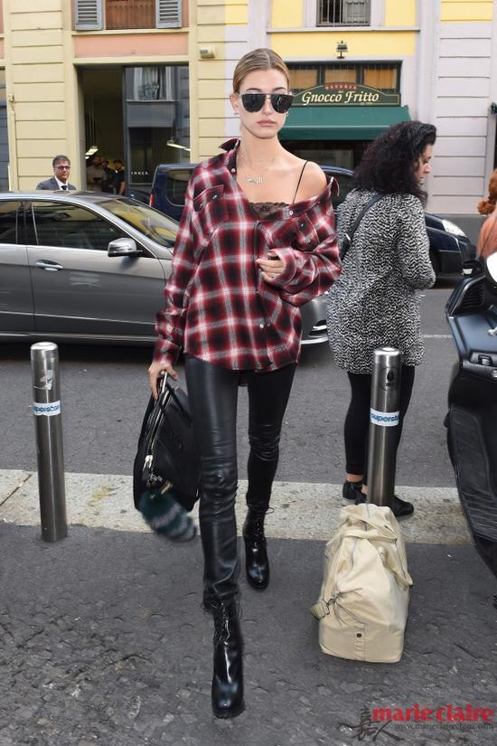 海莉·鲍德温头戴黑色墨镜,身穿红色格纹衬衫,下穿黑色紧身裤,女王气质十足,格子衫的复杂完美衬托了光滑的肩头。