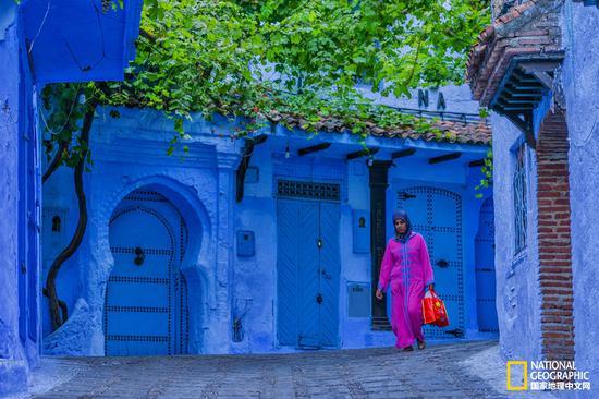 身着桃红色长袍的妇女,行走在蓝色的小巷中,显得格外耀眼。