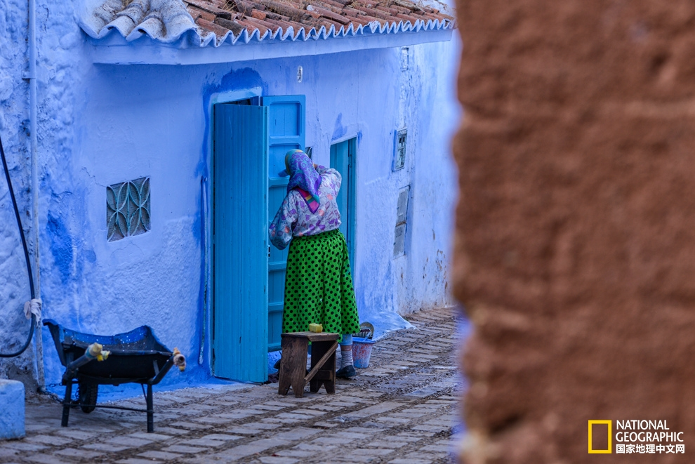 街头转角处一位妇人正在认真给墙壁刷上新鲜的蓝色