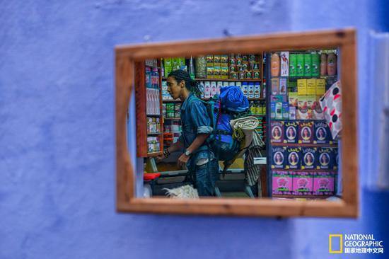 一个背包小哥正在小店买东西。