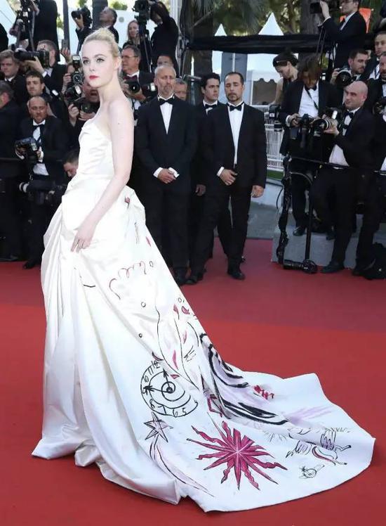 礼服上的图案是工匠手绘的,让一身略有些单调的白裙充满涂鸦的朋克味,Fanning这个真少女穿起来显得趣味十足。