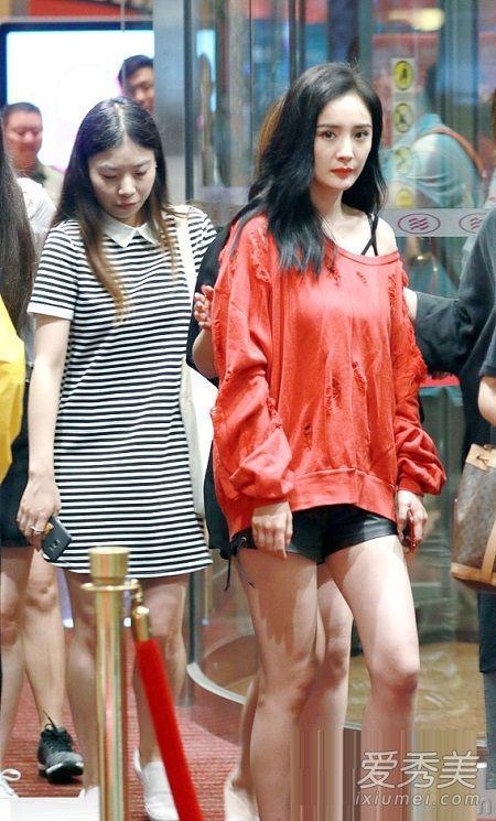 杨幂身穿红色长袖斜肩上衣,搭配黑色皮短裤以及运动鞋,完美秀出了大长腿。