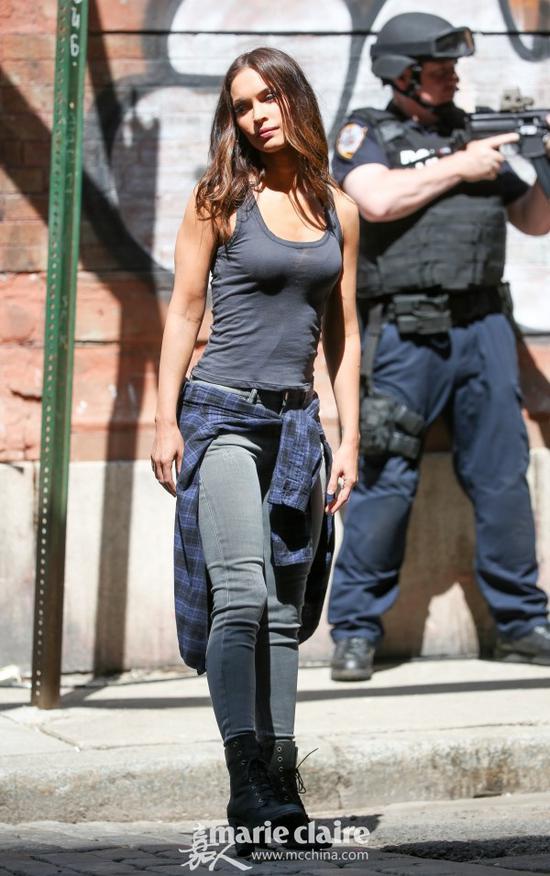 梅根·福克斯(Megane Fox)身穿灰色背心,下配铅笔裤,腰间系着蓝色格纹衬衫,脚踩黑色麂皮粗跟短鞋。