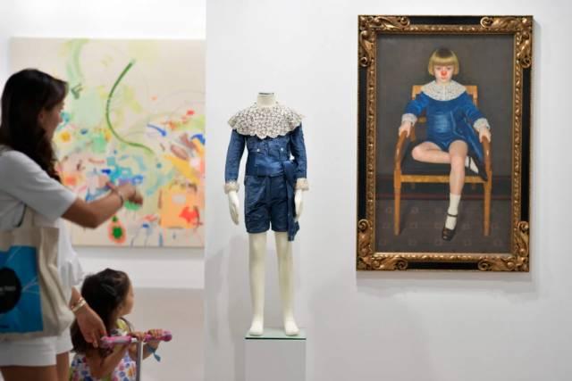 两位参观者正在参观303画廊展位的艺术作品