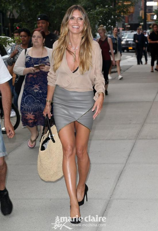 Heidi Klum身穿裸色V领长袖上衣,手拎米色草编大挎包,下穿灰色开叉紧身超短皮裙,脚穿黑色麂皮尖头高跟鞋。