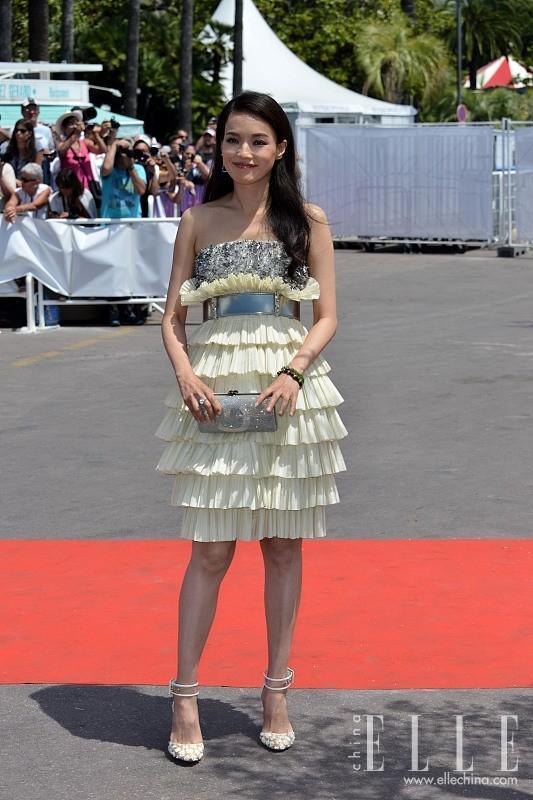 舒淇身穿Chanel银色亮片抹胸层叠荷叶边纱裙,系金属色宽腰带,手拿银色亮钻手包,脚踩淡黄色刺绣系踝高跟鞋,甜美可爱。