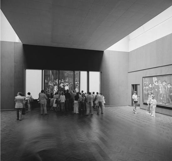 1975-1976年,游客们透过窗户观察《夜巡》的修复进度