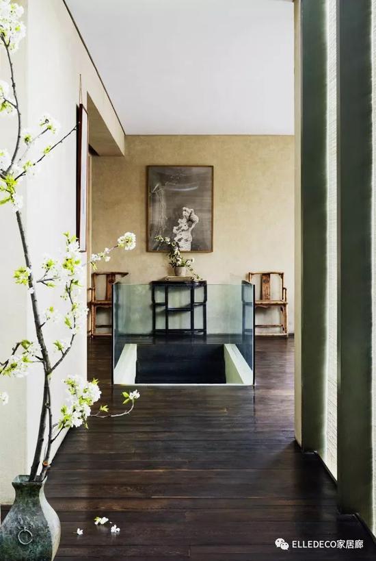 为了空间的通透,楼梯口是由玻璃制成的围栏,二楼地面是原木地板,楼梯上方的山石画来自艺术家师建民。