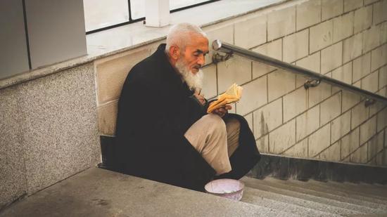 ▲乌鲁木齐,手捧着古兰经的乞讨老人