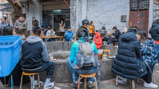 ▲街坊们围坐在水井旁吃早餐。图/图虫·创意