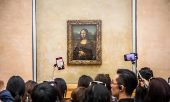 被众多游客环绕的名画《蒙娜丽莎》。图片来源:卫报。