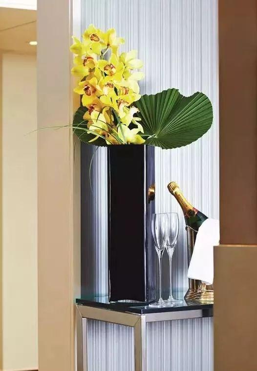 黑色柱状花瓶拉长了花艺造型的比例,黄色的花朵丰富了宾客的视线