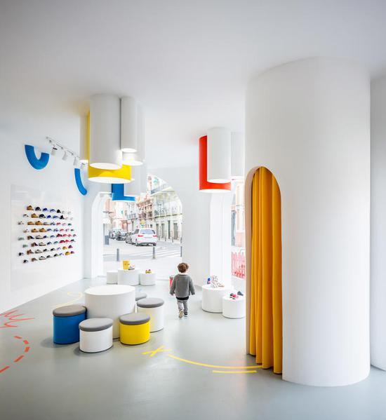 红黄蓝三原色的灯管从天花板向下伸出,分层次地照亮下方的展示柜台。