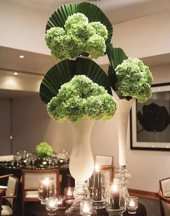 簇团的绿色鲜花组合扇形叶,与白色长条形花瓶搭配装饰,整体造型圆润饱满