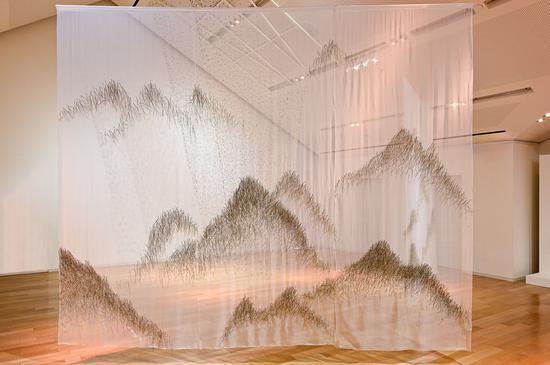 """上海""""爱马仕之家""""《梦之秘境》艺术展——装置《松山》以取自大自然的松针在层层薄纱上编织成图案,营造出雾中远山的景象。"""