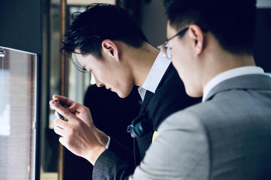 在唐利伟先生的介绍下,李振对珠宝和名表兴趣浓厚,拿出手机拍摄重点拍品