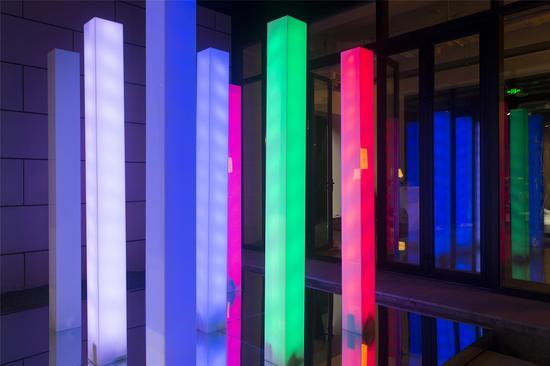 作品名称:《光阵》 作者:李洪祥 材质:综合材料 尺寸:尺寸可变 年代:2019 9根光柱排成 一个矩阵安放在中庭的中央,柱子自身颜色为白色。每一根内部装有受声音控制亮暗变化的LED灯,因此只要声音在矩阵的某个方位响,相邻的几根光柱 就会变亮。LED灯的颜色分为红紫蓝三色系在每根光柱种分别随机变化。 各个尺寸数据可就场地大小做调整。两个相同形状不同颜色的物体以穿透交叉的状态安放在地面上,并且相互穿透对方漏出一块方形的方块,此方块亮着与自己颜色对应的灯光并且以呼吸的频率进行缓慢地亮暗变化。整个装置的表面附上有色镜面膜,最外围的框颜色最纯,向内纯度依次减弱。作品将色彩属性拟人化,给予生命力,在天井空间这样一个与自然沟通的区域形成融合,讨论光作为色彩之源的神秘魅力。