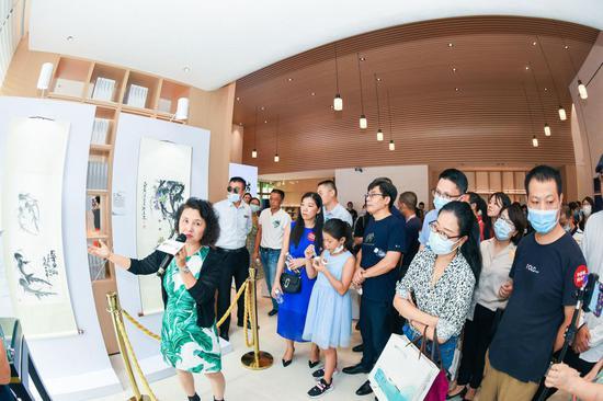 齐艳芳在现场为市民讲解齐家作品及技法特色(左1为齐艳芳《长年有余》-2017)