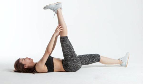 平躺在瑜伽垫上,手握住小腿拉伸大腿后侧,膝盖微曲