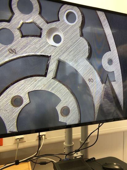 通过显微镜,制表师向我们展示手工倒角的过程