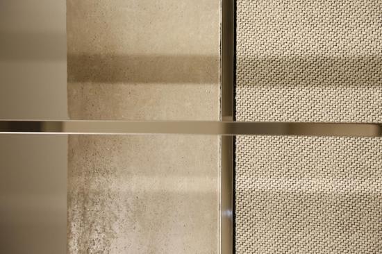 LUCIEN WANG店内银色镜面不锈钢衣架与源自丹麦的墙面布艺装饰形成交错