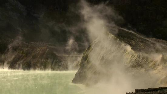 白岛火山的一个小火山口中冒出阵阵烟雾