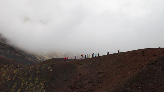 一群游客沿着崎岖的火山岩前行,只为一睹埃特纳火山的真容