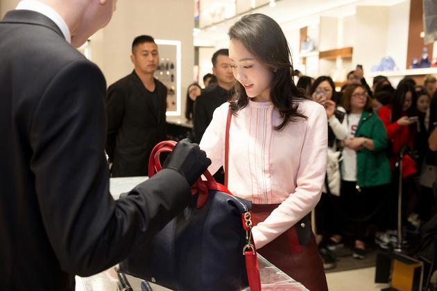 店员向王鸥展示Longchamp新品包包