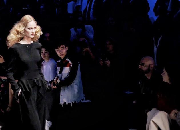 《时尚不死》买手篇的主人公杨晓维在时装周秀场观秀。