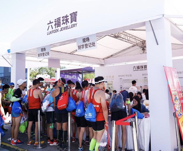 终点处六福珠宝展台免费为选手们进行奖牌刻字服务