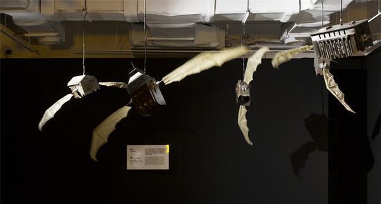 """作品名称:《低语》作者:郑丽镇 材质:金属铁、牛皮、时间继电器 尺寸:500*400*400cm 年代:2017 本作品中,梦想成为一种""""低语"""",联合国五个常任理事国的最高法院建筑物在风中摇曳,缓慢地挥动蝙蝠翅膀,低空飞行。锈迹斑驳的建筑残影面面相觑,窃窃呓语。建筑群缓缓升腾表现出晃晃悠悠的不安,旁观者却可触碰那半透明的羽翼,站在边上,它们似乎在与你讲悄悄话。冷酷的金属色让我们明白了所谓政治语言的超人性运转,不安和冰冷由它传达,个人的梦想和社会性的不可违背由这个寓言所散发。"""