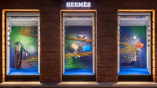 """上海""""爱马仕之家""""携手华人艺术家闫晓静女士,呈现《寄梦》夏季橱窗。男士橱窗中,数千个爱马仕皮革切割而成的3D组件构成一条渐变色彩的旋转""""金色阶梯"""""""