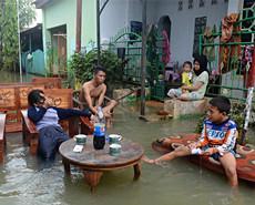 印尼民众洪灾大水中喝可乐 淡定搬家
