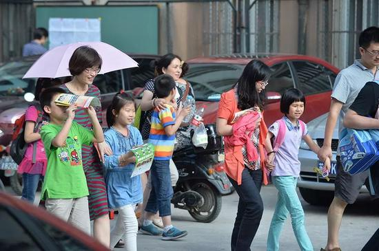 南京,一家教育培训机构楼下接送放学儿童的家长。/ 新华社