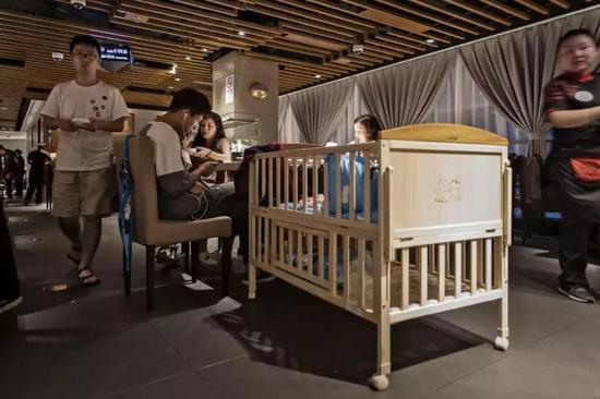 上海一家海底撈餐廳內,餐桌旁放了一個嬰兒牀