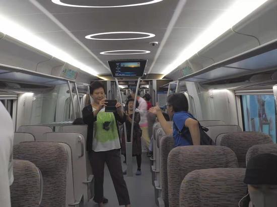 图为大兴机场线地铁车厢内,部分旅客正拍照留念