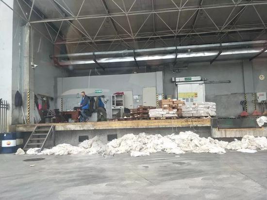 工作人员撕掉走私冻肉外包装上的塑料薄膜,等待客户前来运输。