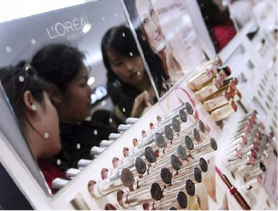 顾客在北京一家商场的欧莱雅专柜试用口红。(彭博新闻社网站)