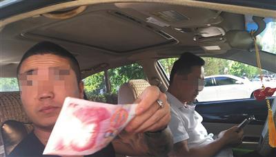 号贩子隔着车窗给一名兼职人员100元作为报酬。