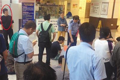 挂号大厅,一名号贩子(圆圈处)被民警认出,让其站在一边,等待被带离。