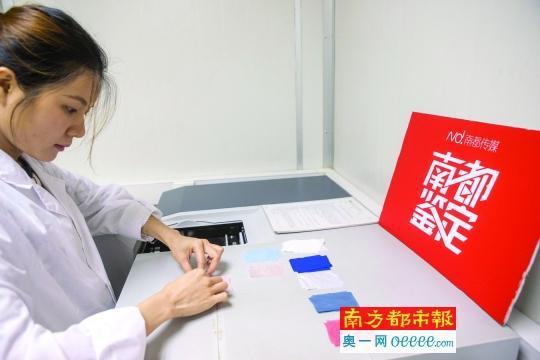 实验员将防晒服的布料样品放入紫外可见分光光度计进行检测。