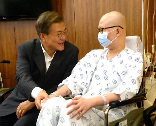 8月9日,文在寅(左)访问位于首尔瑞草区的首尔圣母医院,并与病人亲切交谈。(图片来源:韩联社)