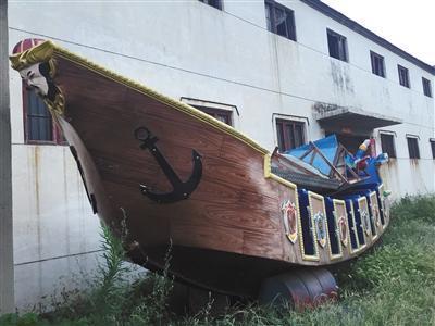 8月13日,河南省荥阳市洼子村一家游乐设备厂的门口,摆放着一艘旧海盗船。厂家称将对其翻新后再出售。A08-A09版摄影/新京报记者 大路