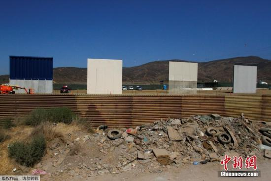 资料图:当地时间2017年10月12日,墨西哥提华纳,从美墨边境墨西哥一侧拍摄到的边境墙样品。特朗普2017年1月25日曾签署行政命令,宣布在美墨边境线上筑墙,以阻挡非法移民和犯罪人员越境从事非法活动。
