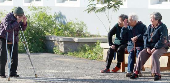 辽宁省沈阳市,幸福老年公寓里晒太阳的老人们相互打招呼。图/视觉中国