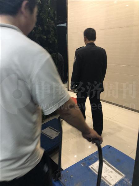 警察在前面引路,搬运人员在后面跟着,到达2楼,是善林金融行政部门的楼层(《中国经济周刊》记者 宋杰 摄)