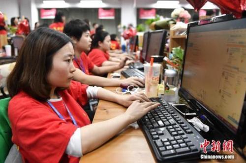 资料图:某电商企业员工们在电脑前解答消费者的购物疑问。中新社记者 陈骥旻 摄