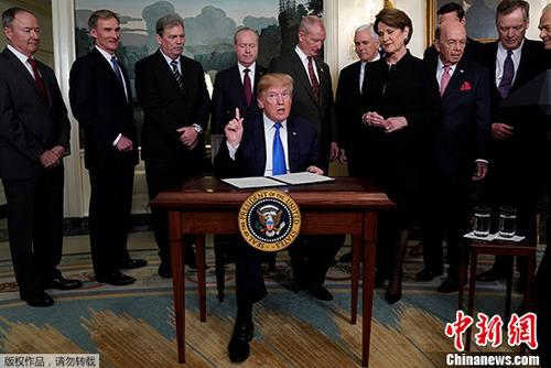 """当地时间2018年3月22日,美国总统特朗普在华盛顿签署总统备忘录,依据""""301调查""""结果,将对从中国进口的商品大规模征收关税,并限制中国企业对美投资并购。特朗普签字前对媒体说,涉及征税的中国商品规模可达600亿美元。"""