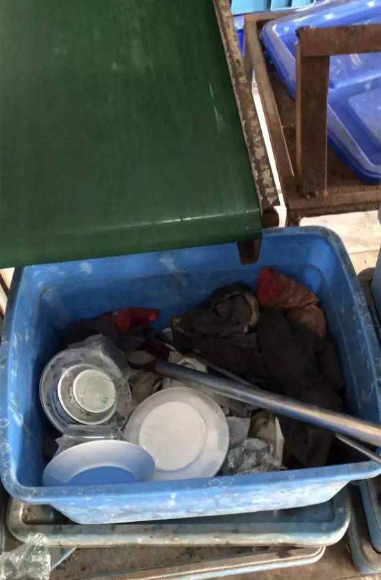 ▲传送带下的箱子里散落着来不及装箱的餐具,里面的脏抹布用来擦抹塑料箱。新京报记者刘经宇 摄
