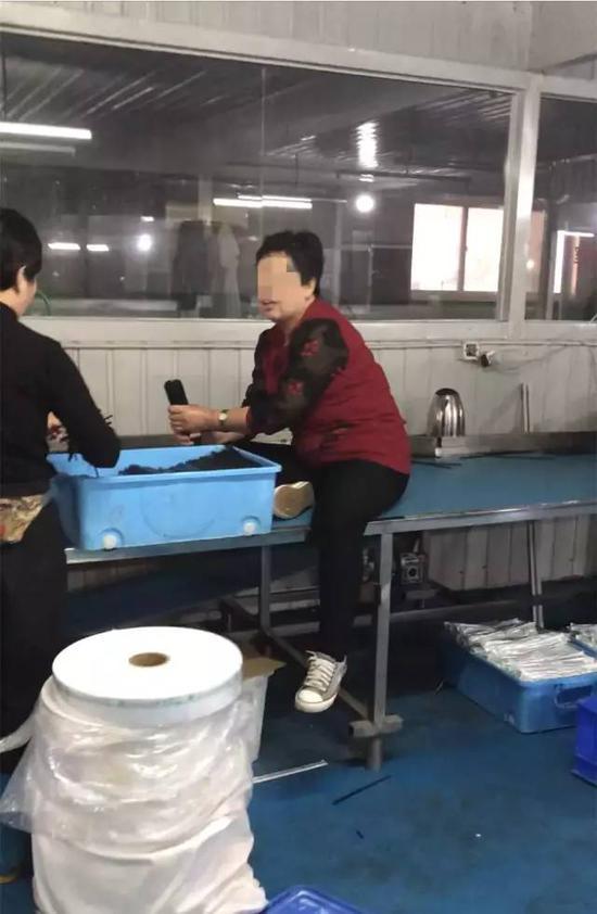 ▲一名工人直接坐在板子上赤手整理洗过的筷子,准备去打包装。新京报记者刘经宇 摄